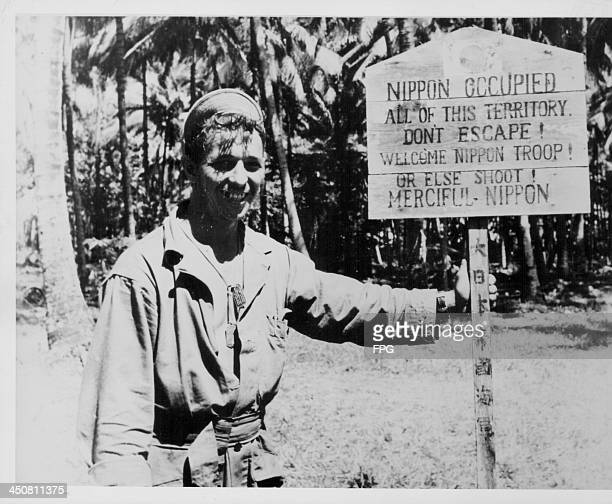 A US soldier posing with a Japanese language signpost in New Britain during World War Two Papua New Guinea circa 19441945