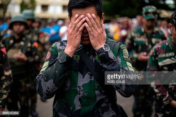 TOPSHOT A soldier prays during a flag raising ceremony at the Lanao Del Sur provincial capital of Marawi on the southern island of Mindanao on June...