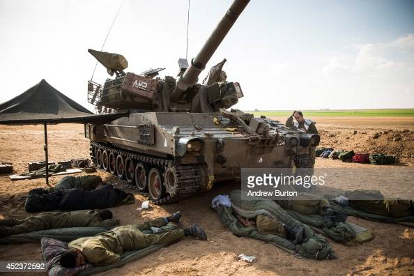 A soldier prays while the rest sleep in the shadow of a tank near the IsraeliGaza border on July 19 2014 near Sderot Israel As operation 'Protective...