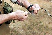 A soldier pulls a detonation cord igniter to start a reaction detonating C-4 explosives.