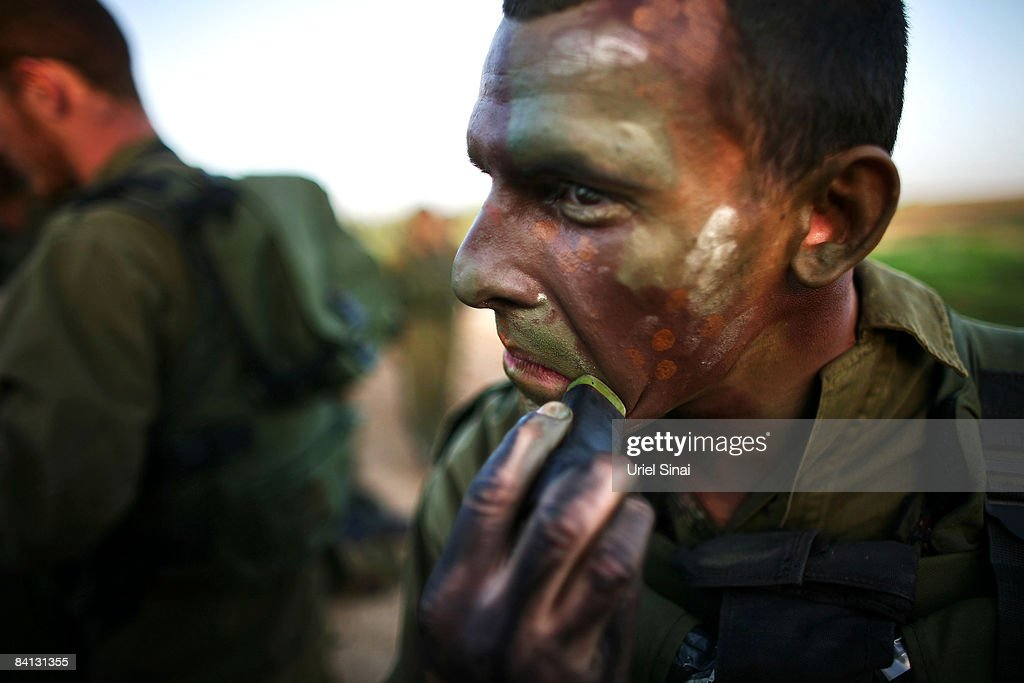 A soldier puts camouflage colors on his face as Israeli army special forces are deployed on December 28 2008 at the Gaza Israel border Israel...
