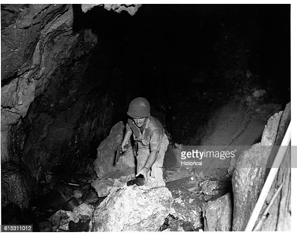 A US soldier reaches for an incendiary bomb left by Japanese troops hiding in the cave on Tinian Island during World War II