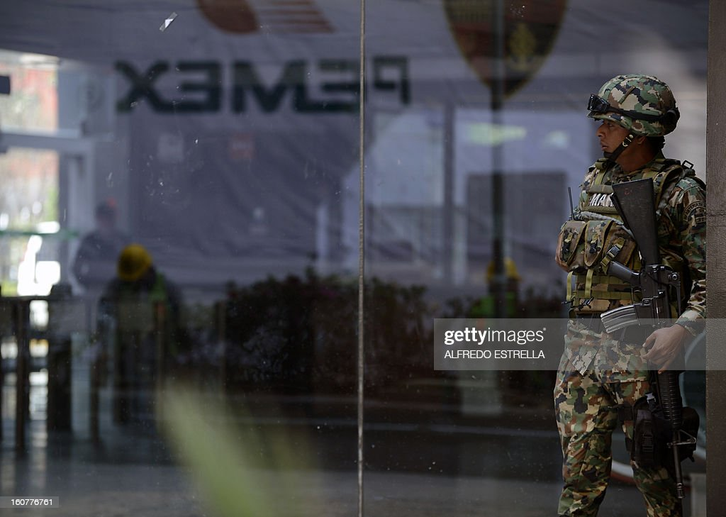 A soldier remains outside the damaged building of Mexican state-owned oil giant Pemex, after a blast, in Mexico City on February 5, 2013. A gas build-up caused the explosion that rocked the headquarters of Mexico's state-owned oil firm last week, killing 37 people, officials said Monday, ruling out a bomb attack. The explosion also injured morfe than 120 people. AFP PHOTO/Alredo Estrella