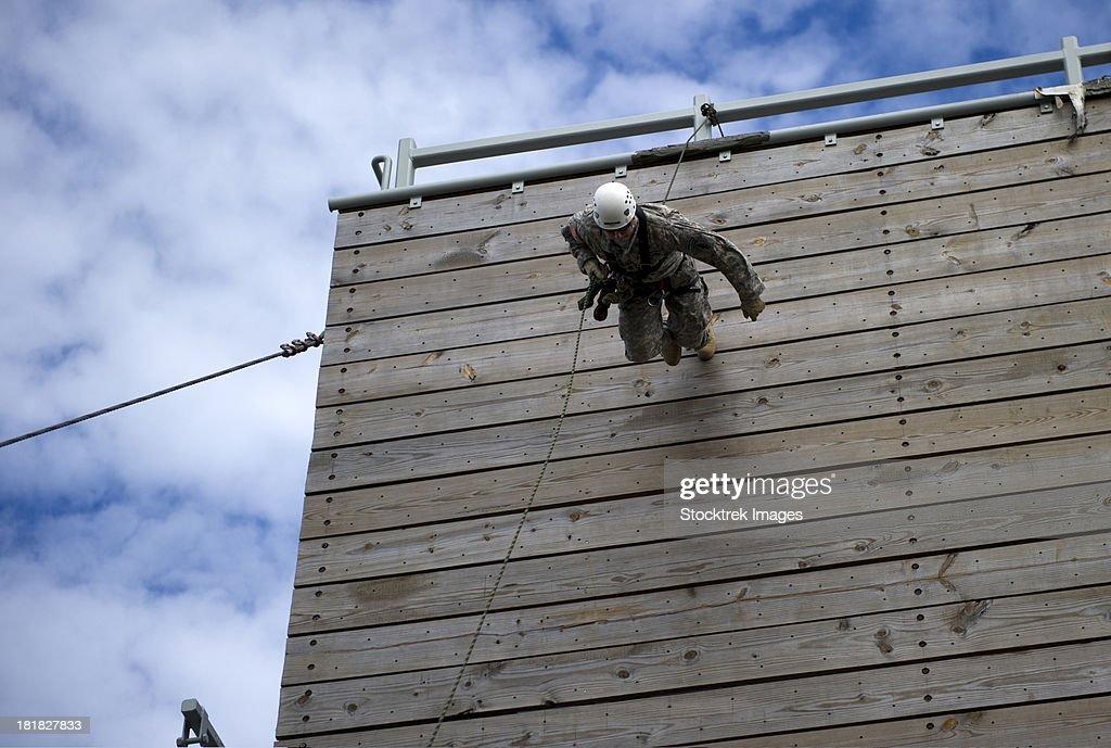 A U.S. Soldier runs down a 40-foot rappelling wall.