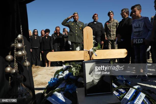 A soldier salutes as other mourners look on over the grave of Georgiou Theodoulos Theodoulou at his funeral on March 5 2017 in Pera Chorio Nisou...