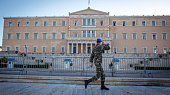 A soldier salutes he passes the Greek parliament building following the electoral success by Syriza in the Greek general election yesterday on...