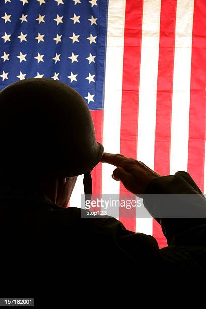WWII Soldier Salutes USA flag wearing field dress uniform. America.