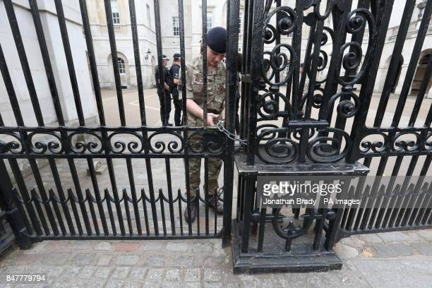 A soldier secures a padlock on gates at the entrance to Horse Guards in Whitehall central London as Operation Temperer is enacted after security...