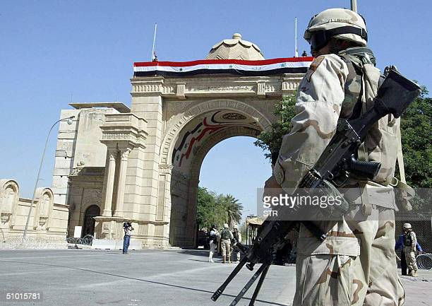 US soldier secures the area prior to the beginning of an Iraqi flag raising ceremony at a former palace of former Iraqi dictator Saddam Hussein 01...