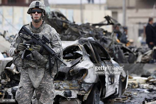 A US soldier secures the site of a bomb blast on Cairo Street in northern Baghdad on December 8 2009 Five powerful car bombs rocked Baghdad killing...
