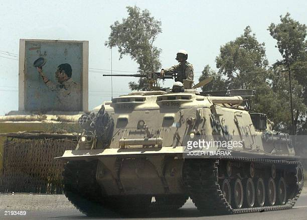 A US soldier sits in his tank next to a defaced mural of toppled Iraqi leader Saddam Hussein in Tikrit 17 July 2003 on the 35th anniversary of the...