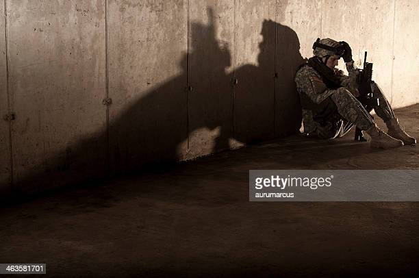 A soldier sitting on the floor with a weapon