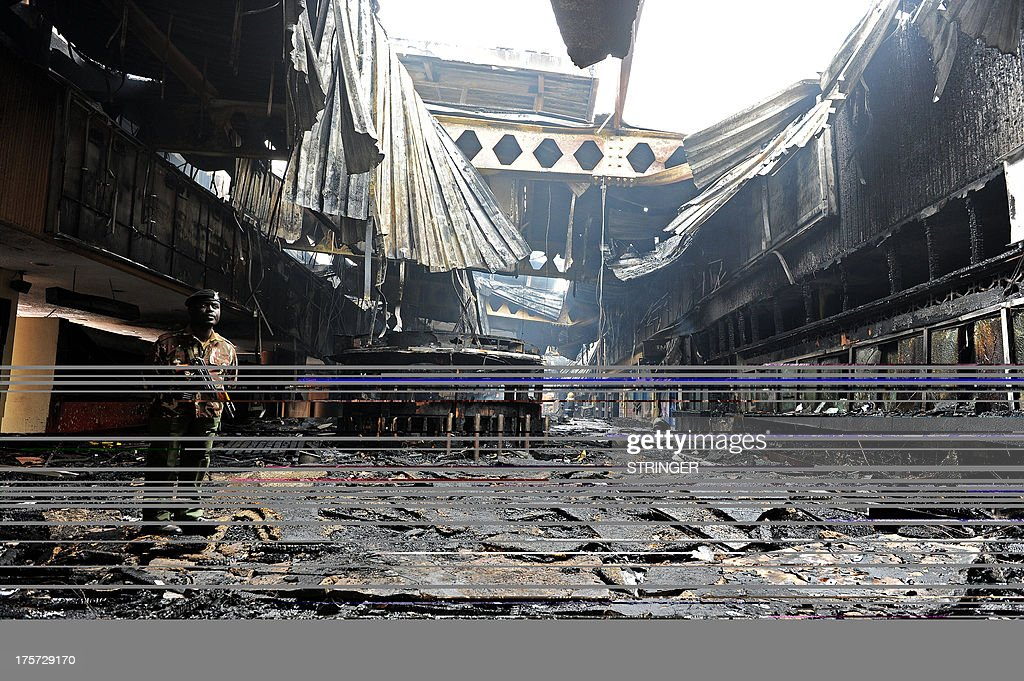 A soldier stands among the debris after a fire damaged a terminal at the Jomo Kenyatta international airport in Nairobi on August 7, 2013. A massive fire shut down Nairobi's international airport on Wednesday with flights diverted to regional cities as firefighters battled to put out the blaze in east Africa's biggest transport hub. Dramatic plumes of black smoke billowed out of the main arrivals terminal, but by 9.00 am (0600GMT), some four hours after the blaze broke out, firefighters had succeeded in stemming the raging flames. AFP PHOTO /Stringer