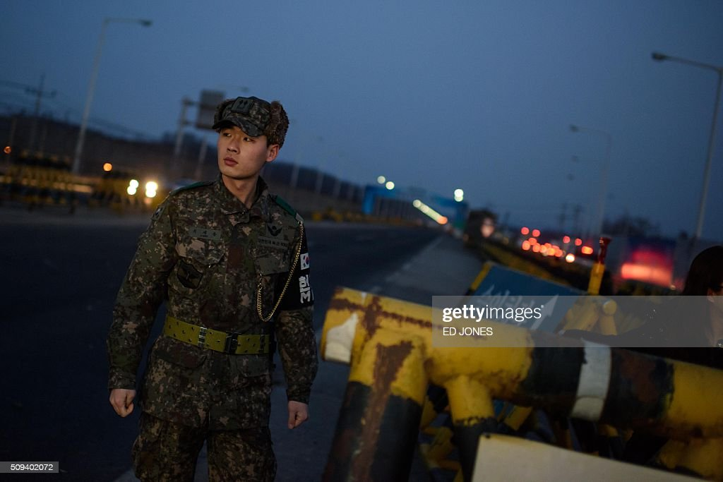 A soldier stands before a barricade at the Tongil bridge, a checkpoint leading to the Kaesong joint industrial zone, in Paju on February 11, 2016. South Korea said it would suspend operations at the Kaesong joint industrial complex in North Korea to punish Pyongyang for its latest rocket launch and nuclear test. / AFP / ED JONES