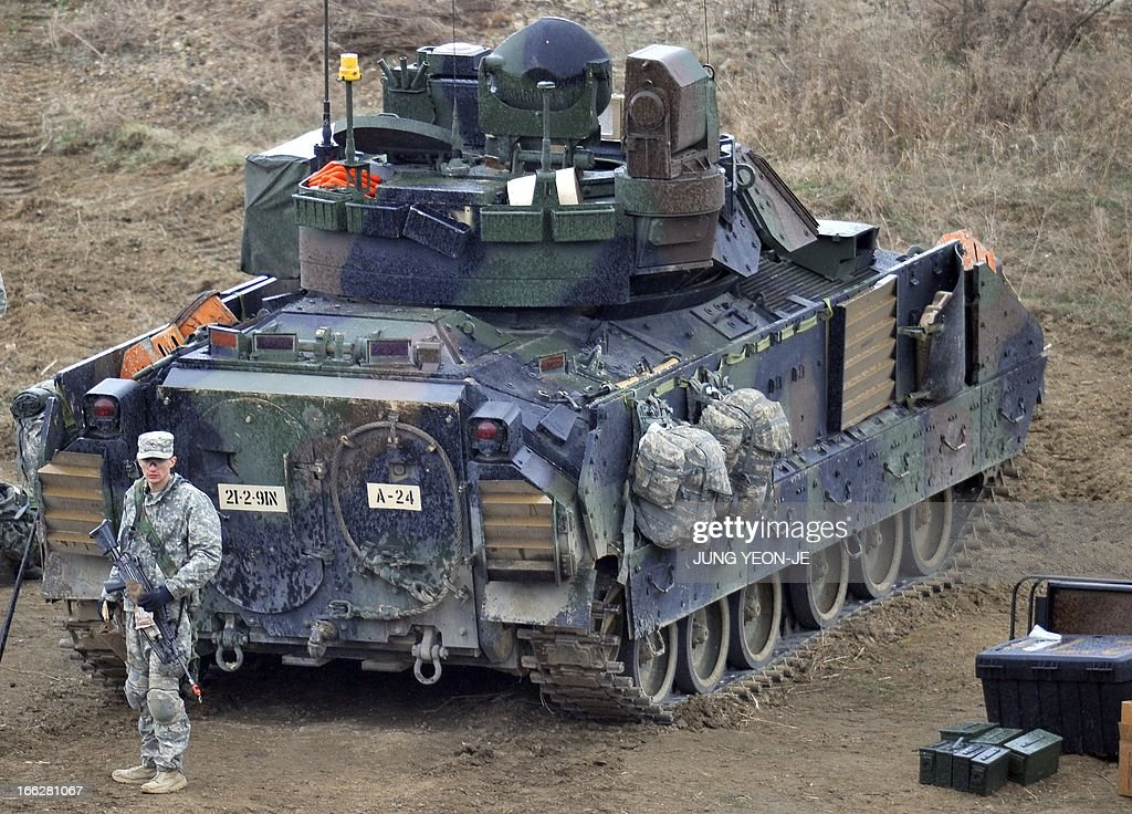 A US soldier stands behind a Bradley armored vehicle at a military training field in the border city of Yeoncheon, northeast of Seoul, on April 11, 2013. The United States has warned North Korea it is skating a 'dangerous line' with an expected missile launch that could start a whole new cycle of escalating tensions in a region already on a hair-trigger.