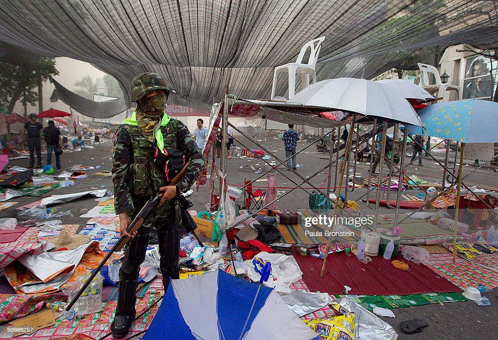 A soldier stands guard after Thai military forces cleared the main rally site inside the red shirt anti-government protesters' camp on May 19, 2010 in Bangkok, Thailand. At least 5 people are reported to have died as government forces sought to overrun barricades raised in and around the city centre by anti-government protestors. Red-shirt leaders have now surrendered, ending their blockade in the aftermath of a sixth day of violence, leaving the army in control and a night time curfew to be imposed.