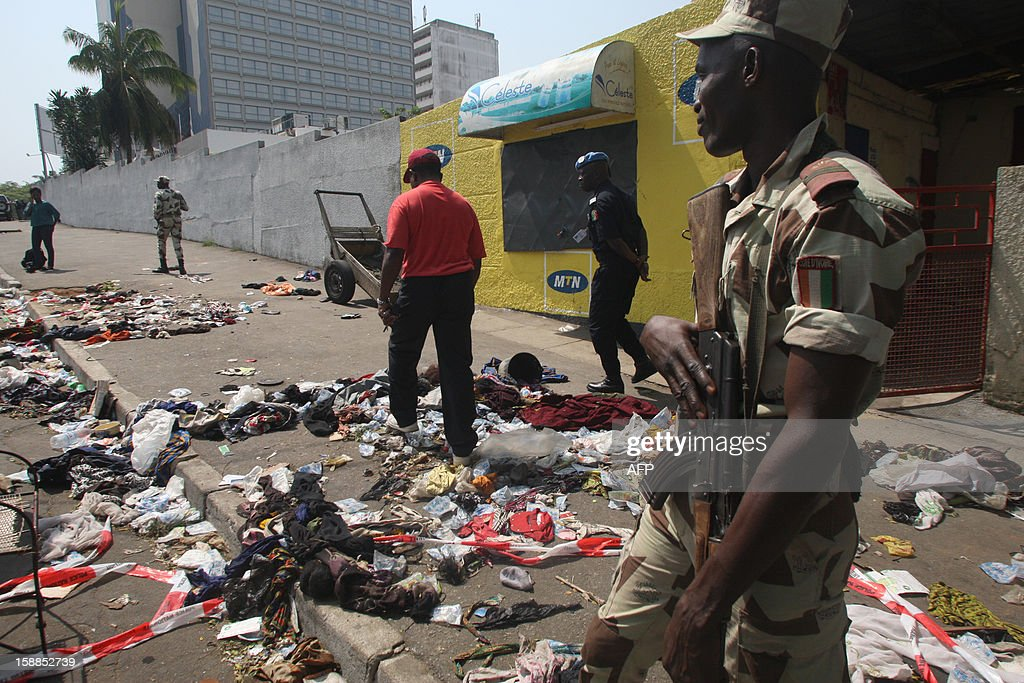 A soldier stands guard as a man walks among clothing and various items spread scattered on the pavement at the scene of a stampede in Abidjan, on January 1, 2013. At least 60 people died and at least dozens were injured as crowds stampeded overnight during celebratory New Year's fireworks, Ivory Coast rescue workers said on January 1, 2013. AFP PHOTO/HERVE SEVI