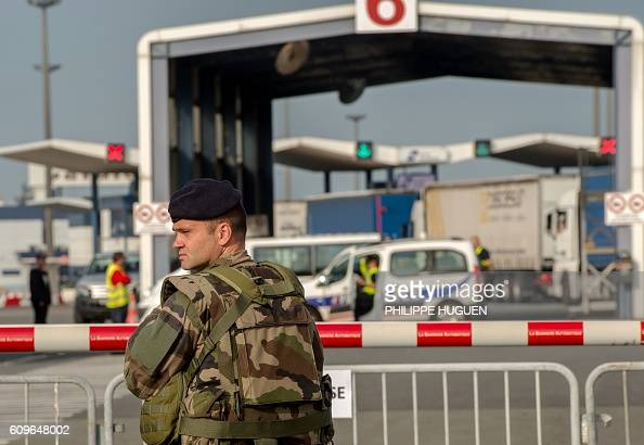A soldier stands guard as policemen search trucks bound for Britain at the ferry terminal of the port of Calais on September 21 2016 / AFP / PHILIPPE...