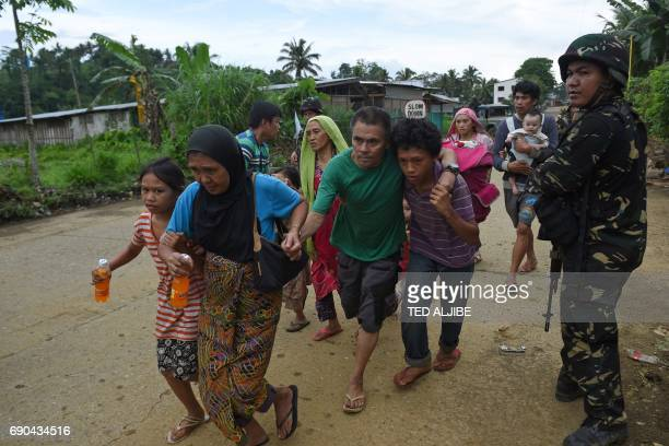TOPSHOT A soldier stands guard as residents runs toward a truck after they were rescued from their homes in a village on the outskirts of Marawi on...