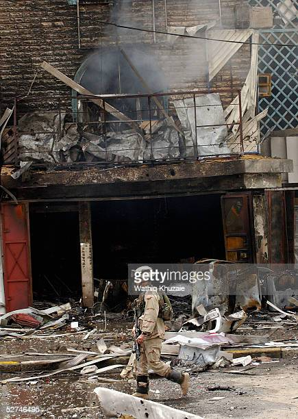US soldier stands guard at the scene of a car bomb explosion outside an electrical goods store in a busy street in the Karradah district on May 2...