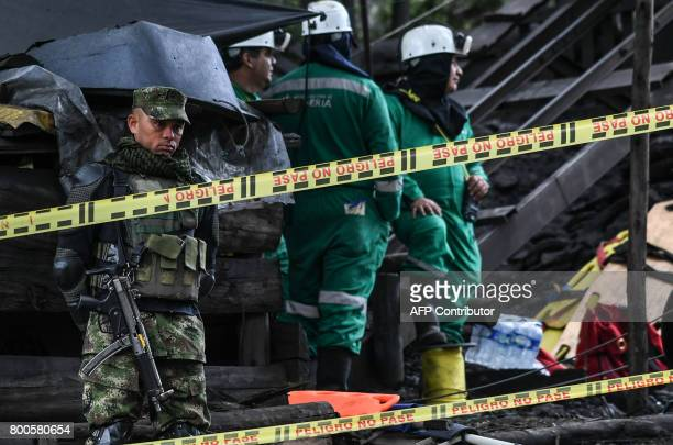 A soldier stands guard during the search operations for missing miners a day after an explosion at the El Cerezo illegal coal mine killed at least...