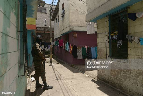 A soldier stands guard in a neighborhood dominated by the Mara Salvatrucha's gang in San Salvador during an operation to take back gangcontrolled...