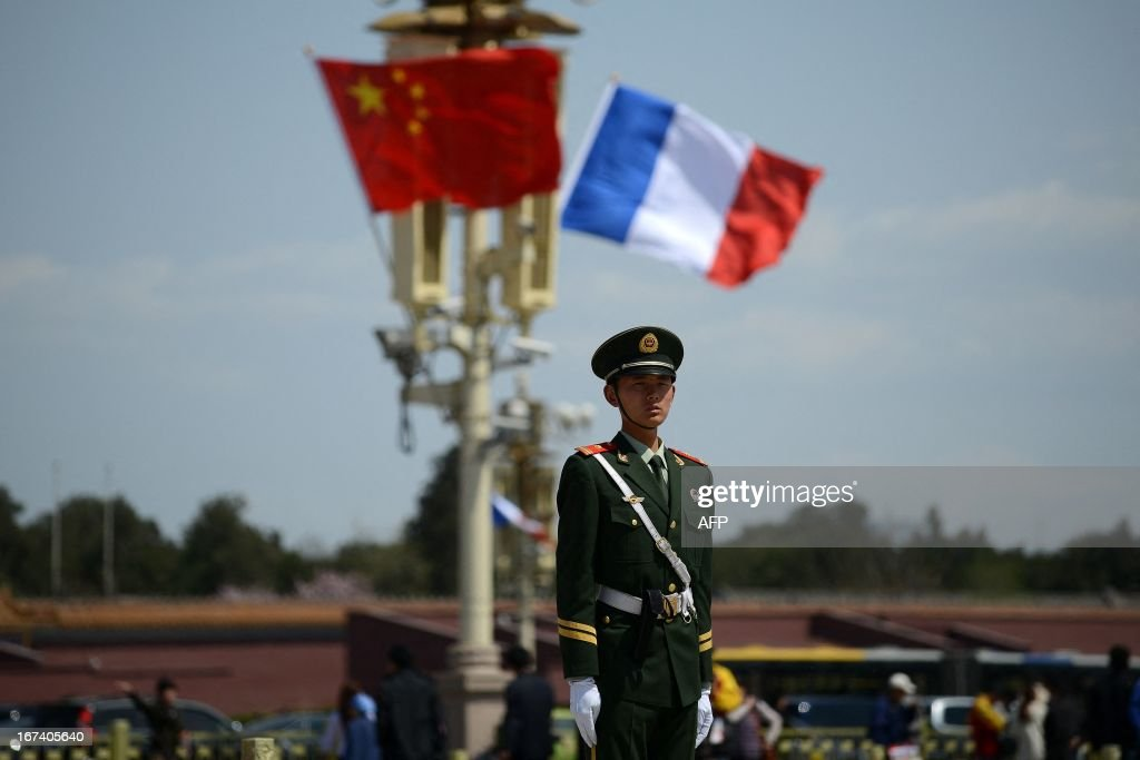A soldier stands guard in front of a French (R) and Chinese national flag (L) at Tiananmen square in Beijing on April 25, 2013. French President Francois Hollande arrived in Beijing on April 25 on a trip aimed at boosting exports to China, with hopes that deals can be reached over the sale of aircraft and nuclear power. AFP PHOTO / WANG ZHAO