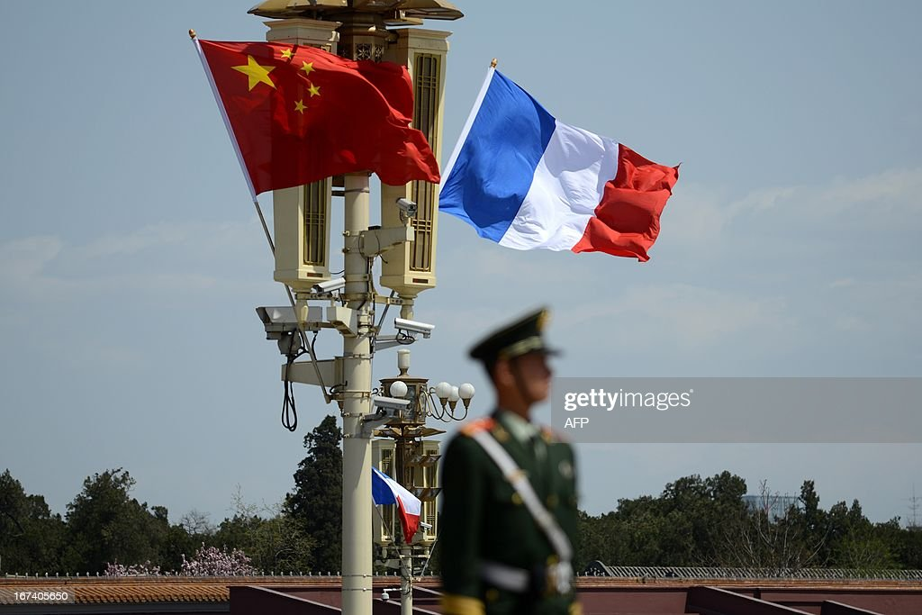 A soldier stands guard in front of a French (R) and Chinese national flag (L) at Tiananmen square in Beijing on April 25, 2013. French President Francois Hollande arrived in Beijing on April 25 on a trip aimed at boosting exports to China, with hopes that deals can be reached over the sale of aircraft and nuclear power.