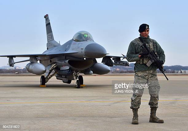 A US soldier stands guard in front of a US F16 fighter jet after a press briefing on the flight by a US B52 Stratofortress over South Korea at the...