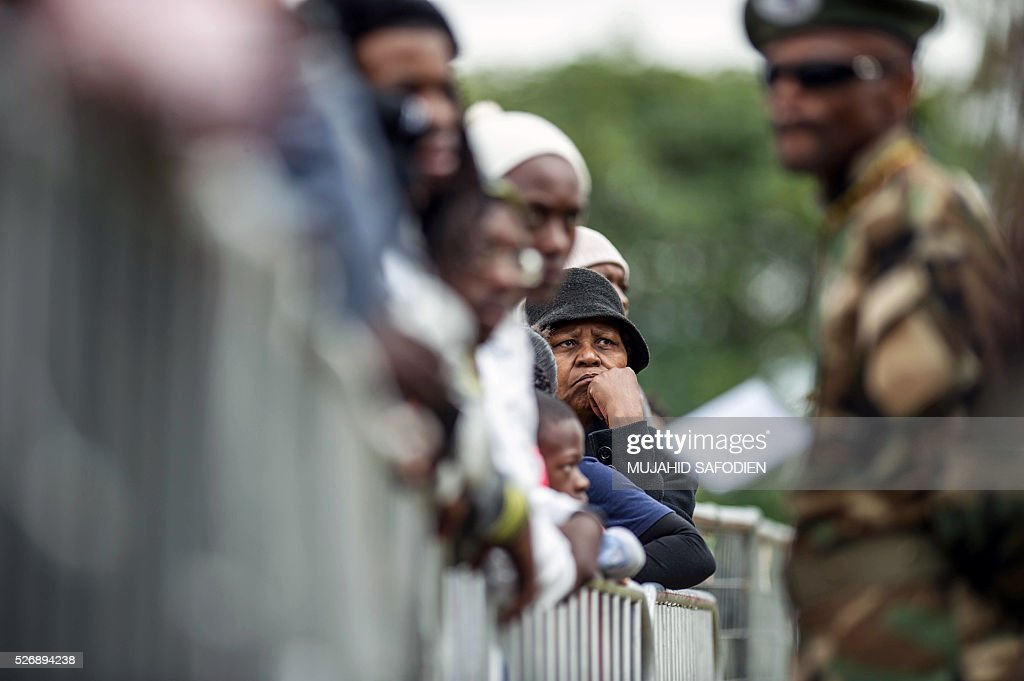 A soldier stands guard in front of participants in the congress of South African Trade Unions (COSATU) attending the May Day rally at Mamelodi's Moreleta park on May 1, 2016 in Pretoria. Secretary General Sdumo Dlamini, South African Communist Party leader Blade Nzimande and South African President Jacob Zuma took part in the rally. / AFP / MUJAHID