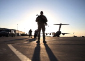 A soldier stands guard near a C17 military aircraft sitting on the tarmac on December 8 2013 in Kandahar US Defense Secretary Chuck Hagel told...