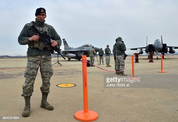 A US soldier stands guard near a US F16 fighter jet and a South Korea F15K fighter jet before a press briefing on the flight by a US B52...