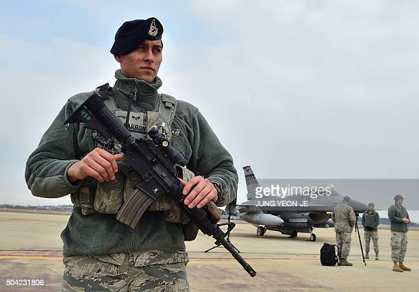 A US soldier stands guard near a US F16 fighter jet before a press briefing on the flight by a US B52 Stratofortress over South Korea at the Osan Air...