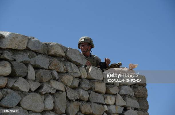 A US soldier stands guard near the site of a US bombing during an operation against Islamic State militants in the Achin district of Nangarhar...