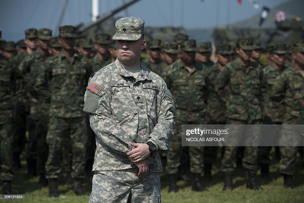 A US soldier (front) stands in front of a line of Thai soldiers (back) during the opening ceremony of Cobra Gold 2016 in Sattahip on February 9, 2016. Thailand and the US jointly host Cobra Gold Asia's largest military exercise from February 9 to 20. AFP PHOTO / Nicolas ASFOURI / AFP / NICOLAS ASFOURI