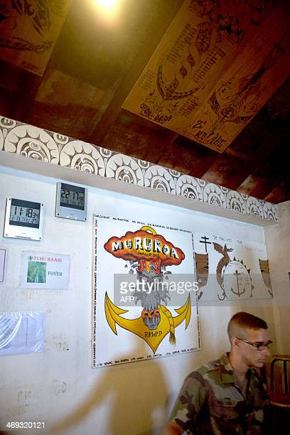 A soldier stands in front of a wall covered with posters representing various temporary unity emblems in the 'Martine' life base in the north zone of...