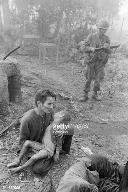 A soldier stands nearby as a Vietnamese father cradles his dead son in Bon Son Vietnam The child was killed during fighting between the US First...