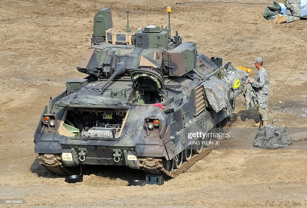 A US soldier stands next to a Bradley armored vehicle at a military training field in the border city of Yeoncheon, northeast of Seoul, on April 9, 2013. North Korea said on April 9 the Korean peninsula was headed for 'thermo-nuclear' war and advised foreigners in South Korea to consider evacuation -- a warning that was largely greeted with indifference.