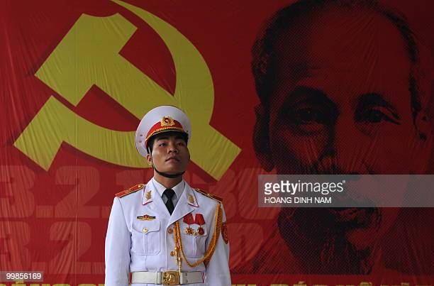A soldier stands next to a large poster with portrait of late president Ho Chi Minh at the venue of an official ceremony in Hanoi on May 18 2010 to...