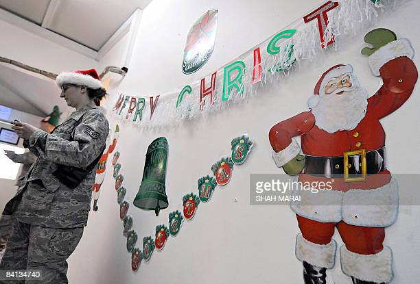 A US soldier stands next to a wall adorned with Christmas decorations at a mess hall in Camp Eggers in Kabul on December 25 2008 International...