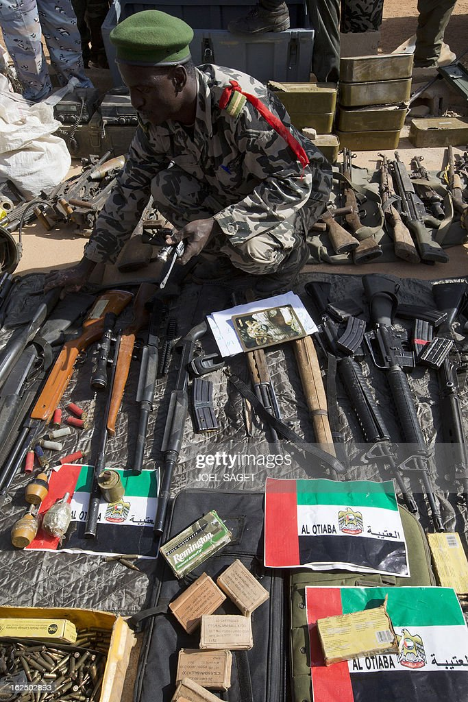 A soldier stands next to weapons and ammunitions seized from Islamist fighters exhibited with flags from the United Arab Emirates by the Malian army in the centre of Gao on February 24, 2013. Tuareg militias battled Arab rebels in northern Mali Saturday, while French jets, US drones and Chad's elite desert forces were also in action in a major push to stamp out resistance from pockets of Islamist fighters. After recapturing the north's cities from the Al Qaeda groups that had controlled them since April 2012, the six-week-old French-led offensive took the fight to the retreating Islamist insurgents' toughest desert bastions. AFP PHOTO /JOEL SAGET