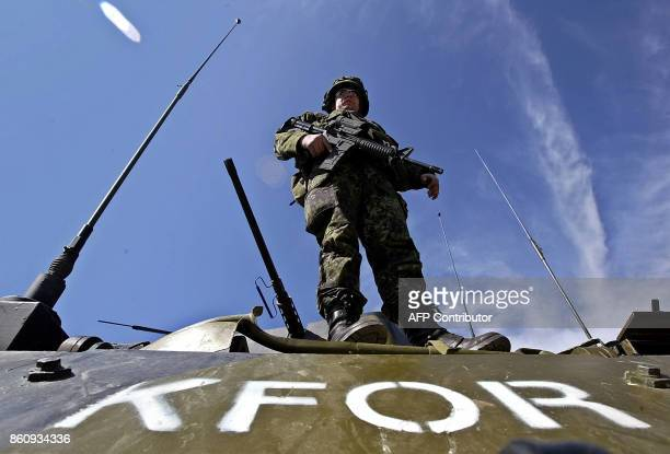 A KFOR soldier stands on an armoured vehicle as UN troops block all access to the ethnic Albanian village of Cabra 10km west of the flashpoint city...