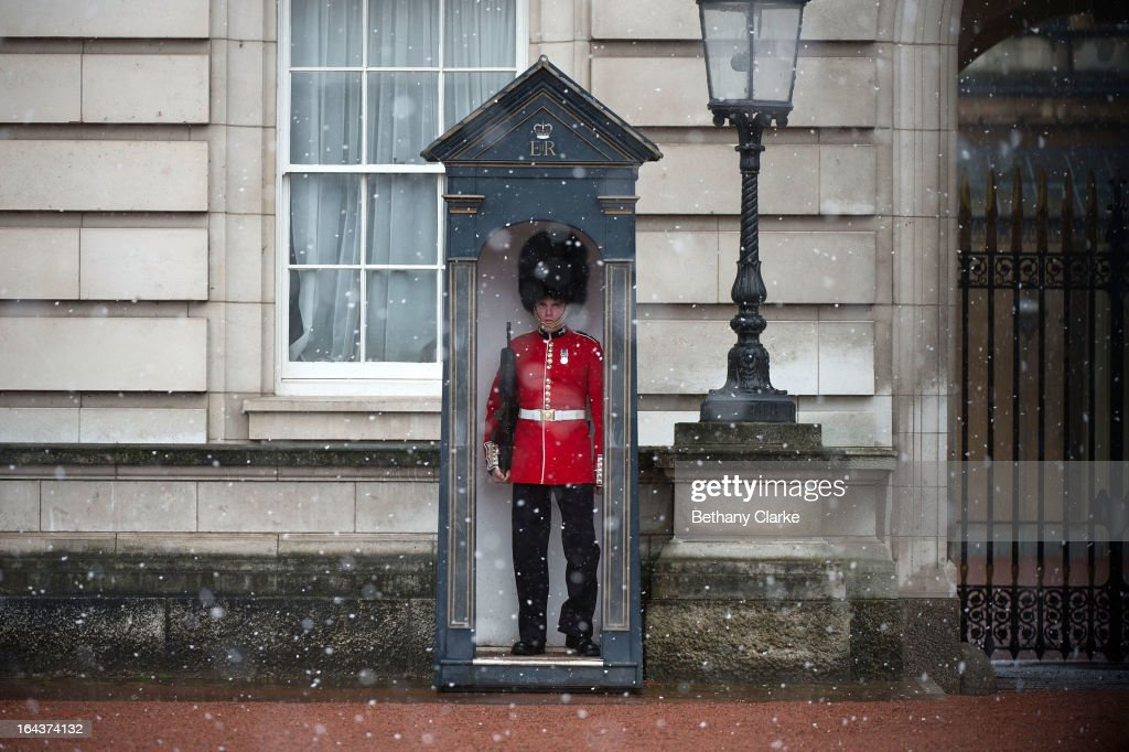 A soldier stands on guard during a snow shower on the first day the soldiers are wearing their summer red tunics outside Buckingham Palace on March 23, 2013 in London, United Kingdom. The UK is facing another day of severe weather disruption, with flood and snow warnings issued in a number of regions across the country.