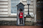 A soldier stands on guard during a snow shower on the first day the soldiers are wearing their summer red tunics outside Buckingham Palace on March...