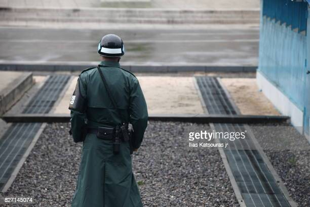 Soldier stands on guard in the rain, in front of border between North and South Korea
