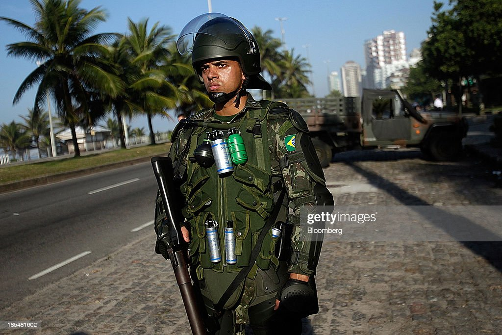 A soldier stands outside the Windsor Barra Hotel in Rio de Janeiro, Brazil, on Monday, Oct. 21, 2013. Soldiers, army vehicles, helicopters and navy ships are guarding a Rio de Janeiro hotel where companies including China National Petroleum Corp., Royal Dutch Shell Plc and Total SA are expected to vie for one of the worlds two largest offshore fields at 3 p.m. local time, as oil workers protest the concession. Photographer: Dado Galdieri/Bloomberg via Getty Images