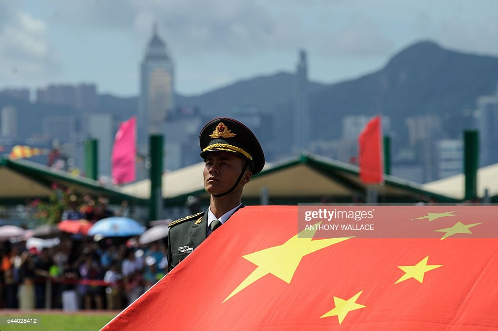 A PLA soldier stands to attention with the Chinese flag during the open day of the Chinese People's Liberation Army (PLA) Navy Base at Stonecutter Island in Hong Kong on July 1, 2016, to mark the 19th anniversary of the Hong Kong handover to China. / AFP / Anthony Wallace
