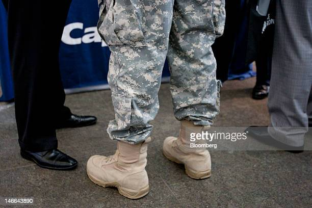 A soldier stands with recruiters from a bank at the Veterans On Wall Street job fair in New York US on Thursday June 21 2012 More Americans than...