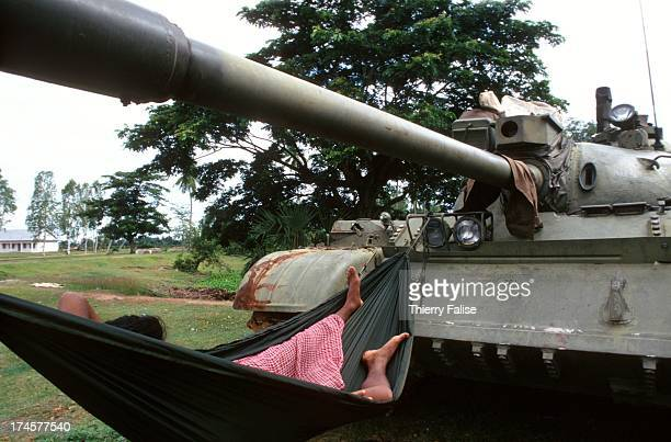 A soldier takes a nap in a hammock tied to the canon of a tank parked on the road from Siem Reap to Sisophon during the 1997 coup d'etat