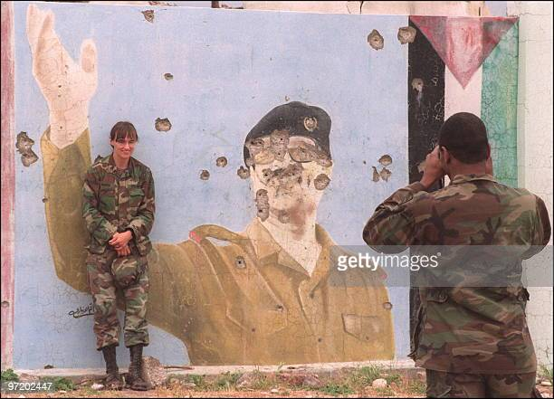 US soldier takes a picture of his female colleague posing in front of a huge graffiti portrait of Iraqi President Saddam Hussein 01 May 1991 in Zakho